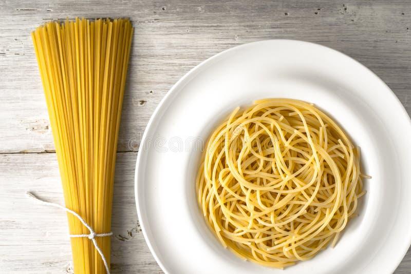 Rå och lagad mat spagetti på den horisontalvita trätabellen royaltyfria foton