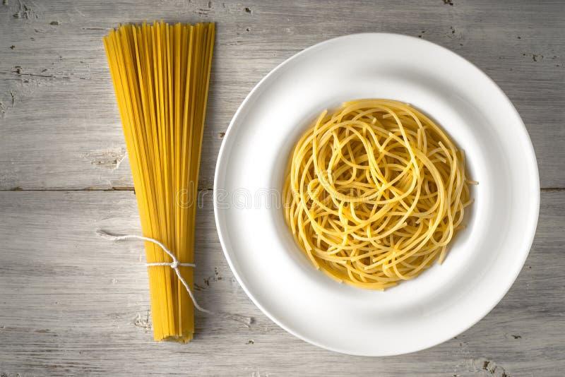 Rå och lagad mat spagetti på den vita träbästa sikten för tabell arkivfoton
