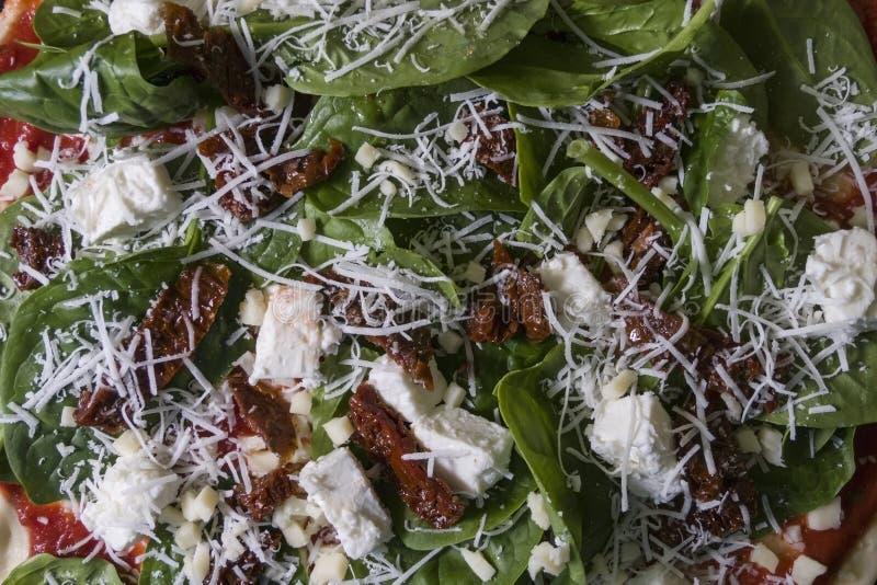 Rå okokt pizza med spinache torkade tomater och fetaost arkivbilder