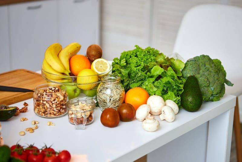 Rå organiska grönsaker, frukter och muttrar med nya ingredienser för healthily att laga mat på kök Strikt vegetarian eller bantar arkivfoton