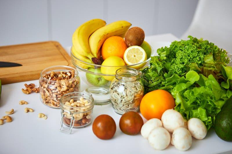 Rå organiska grönsaker, frukter och muttrar med nya ingredienser för healthily att laga mat på kök Strikt vegetarian eller bantar royaltyfri bild