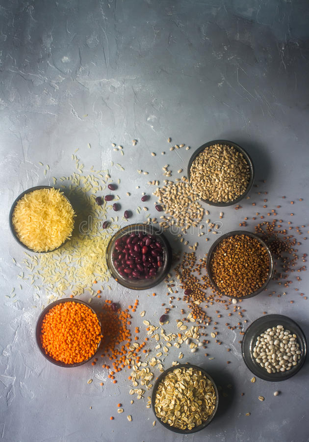 Rå organiska sädes- korn, frö och bönor på mörk stenbakgrund, utrymme för text arkivfoton