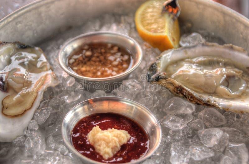 Rå ostron på is med såser och citronen arkivfoto