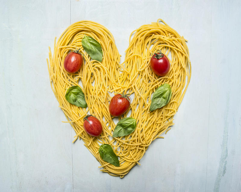 Rå pasta med körsbärsröda tomater och basilikasidor fodrade upp hjärta, valentindag på trälantligt slut för bästa sikt för bakgru royaltyfria foton
