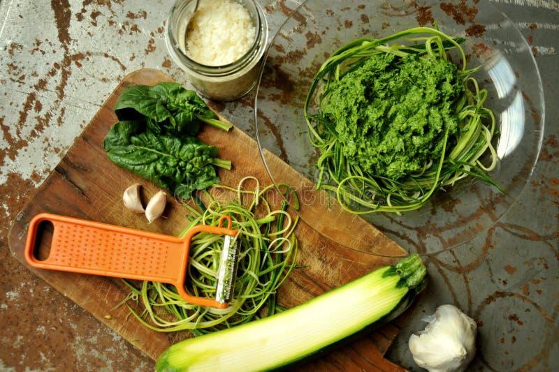 Rå pasta med zucchini- och spenatpesto med vitlök arkivbilder