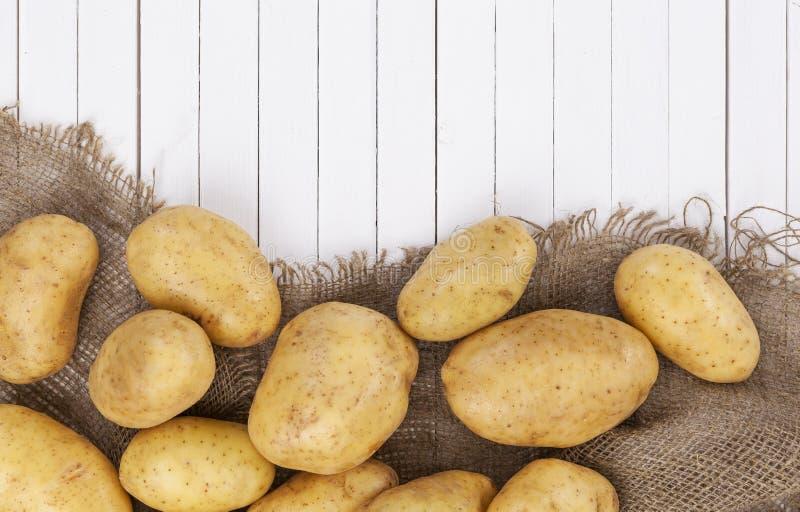 Rå potatis, hög av potatisar på säckväv på den vita trätabellen royaltyfri foto