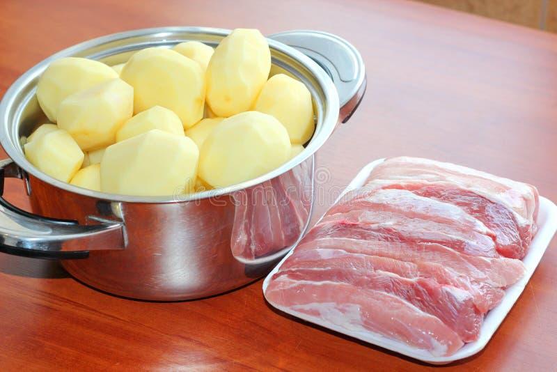 Rå potatisar för kött Kruka med potatisar arkivfoto