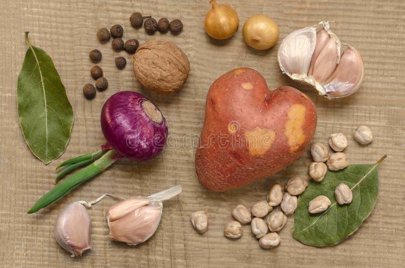 Rå potatisar och kryddor, på den gamla träyttersidan royaltyfri bild