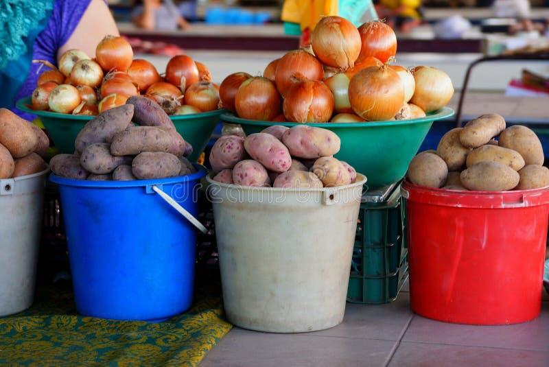 Rå potatisar och lökar i hinkar på en tabell i marknaden royaltyfri foto