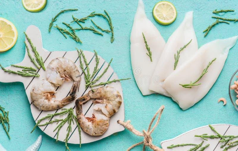 Rå räka eller räkor och tioarmade bläckfiskar på ljus - blå bakgrund som dekoreras med med havsväxter och citronen, bästa sikt, l royaltyfria foton