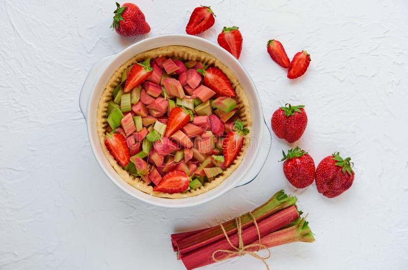 Rå rabarberjordgubbepaj som är klar för att laga mat i den stekheta maträtten på det vita köksbordet med nya ingredienser fotografering för bildbyråer