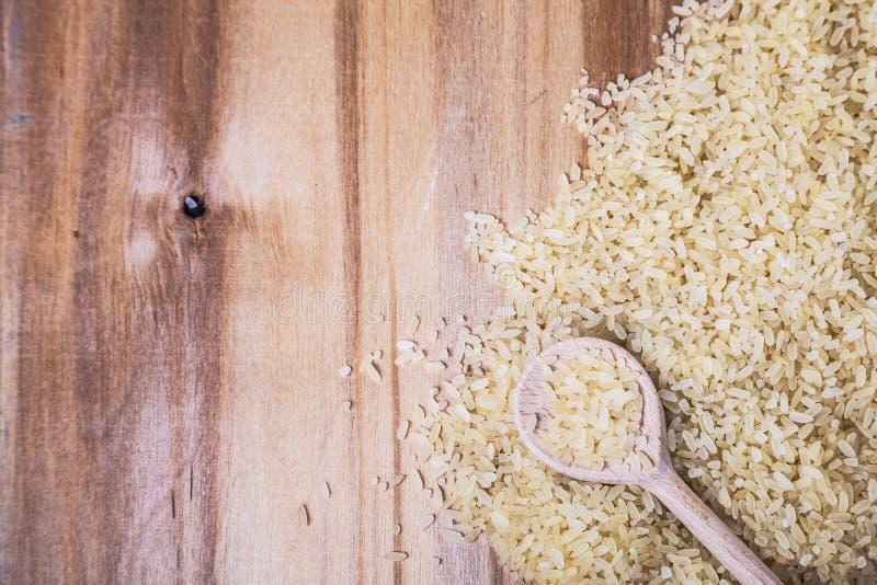 Rå ris i en träsked royaltyfri fotografi