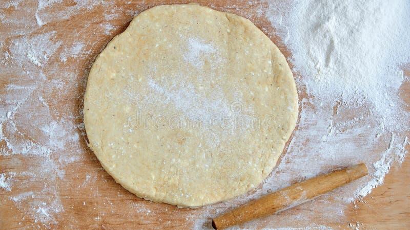 Rå rund deg för pizza eller paj med kavlen och spritt mjöl på träköksbordet Stekhet bakgrund royaltyfria foton