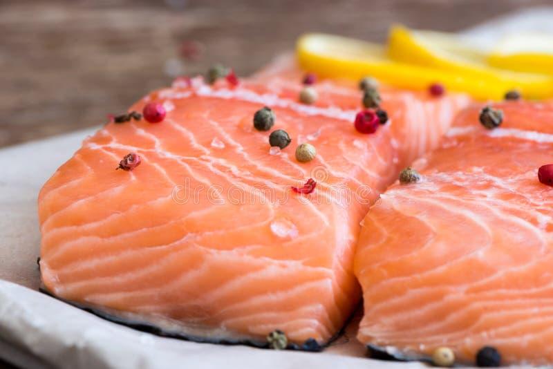 Rå Salmon Fish Fillet med citronen och kryddor arkivbild