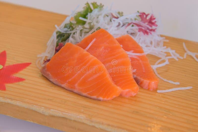 Rå sashimiskivor för lax av rökt på träplattan royaltyfri bild