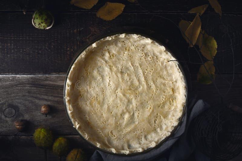 Rå shortcrustbakelse i den stekheta maträtten på den träbästa sikten för tabell arkivfoton