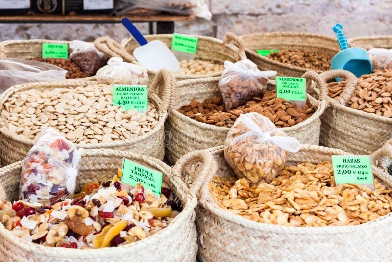 Rå skalade mandlar, torkade tropiska frukter, rå mandlar med hud och stekte rimmade bondbönor på Sineu marknadsför royaltyfria bilder