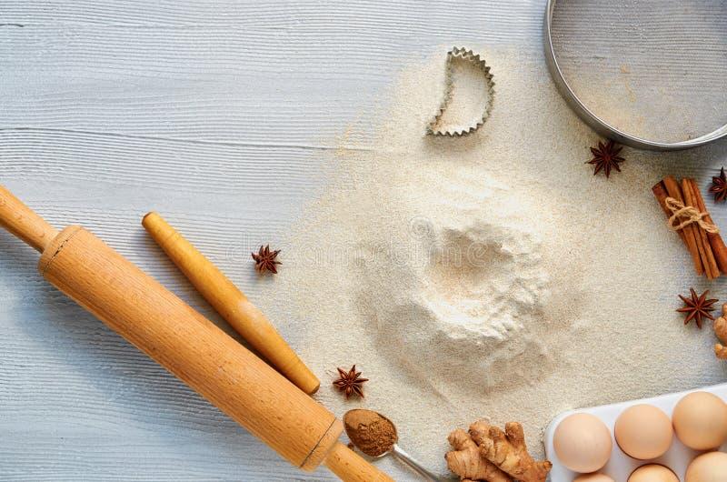 Rå stekheta ingredienser och tillbehör för deg med kopieringsutrymme: kavel, ägg, ingefära, anisstjärnor, kanel och bakewares royaltyfri foto