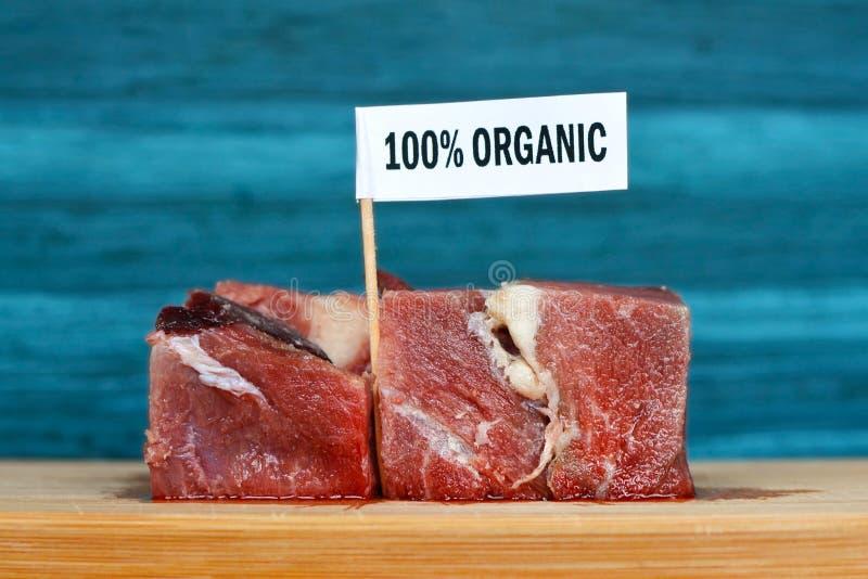 Rå stora köttstora bitar på träplattan med etiketten som säger '100 procent porganic ', begrepp för sund organisk livsmedelsprodu royaltyfri fotografi