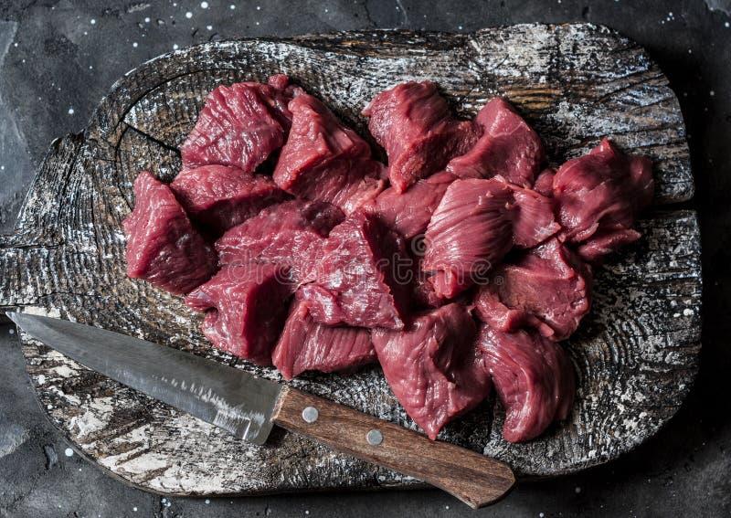 Rå stycken för nötköttfilékött för ragu på en trälantlig skärbräda på mörk bakgrund, bästa sikt royaltyfri bild