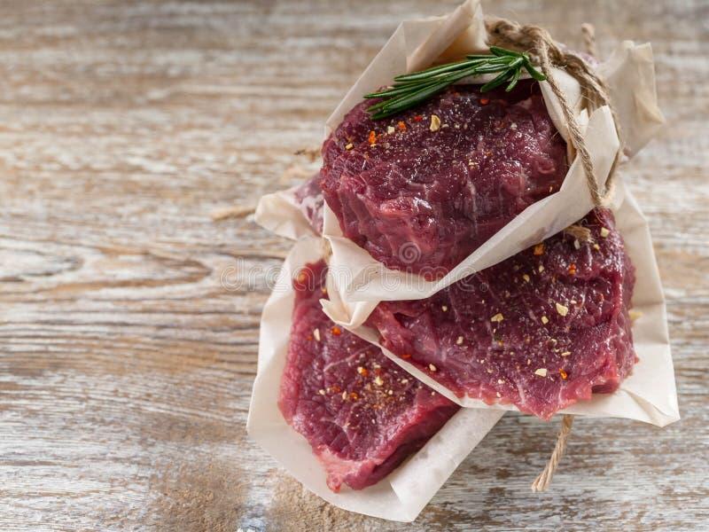 Rå svarta Angus Beef Steaks på träbakgrund Kött, kryddor och rosmarin royaltyfri fotografi