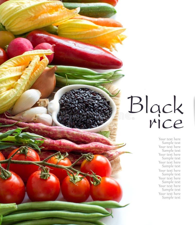 Rå svarta ris i en bunke och nya grönsaker royaltyfri foto