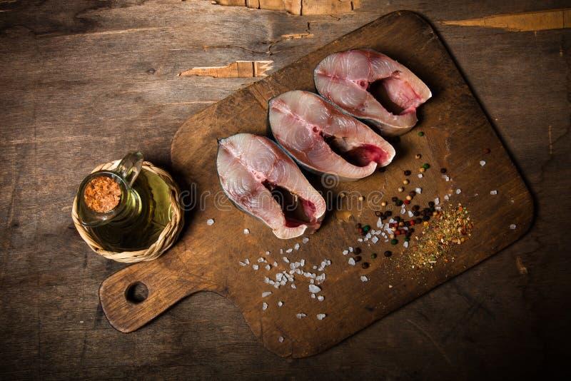 Rå tonfiskfisk och kryddor för att laga mat på en gammal träbakgrund royaltyfria bilder