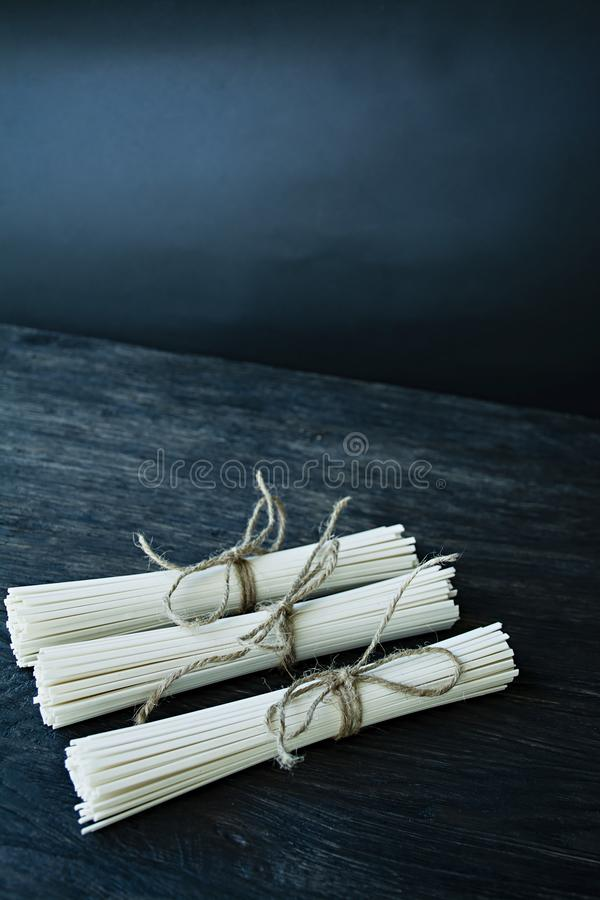 Rå udonnudlar i rullar på en mörk träbakgrund placera text Slapp fokus royaltyfri fotografi