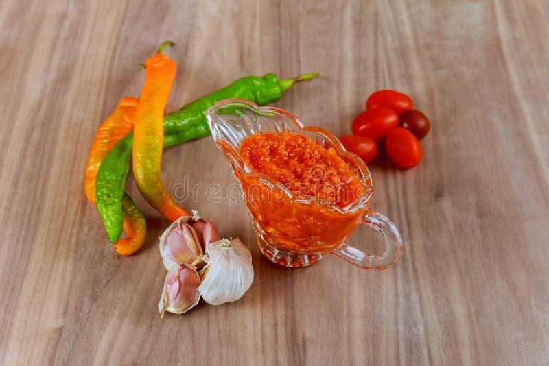 Rå varm georgian såsadjika och ingredienser på en trätabell royaltyfri fotografi