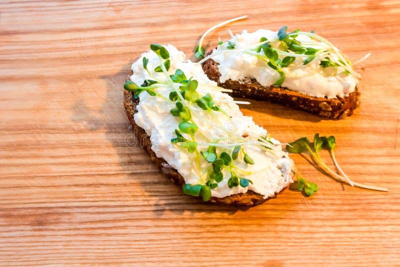 Rågbröd med ostmassarädisan på ett brunt träbräde arkivbilder