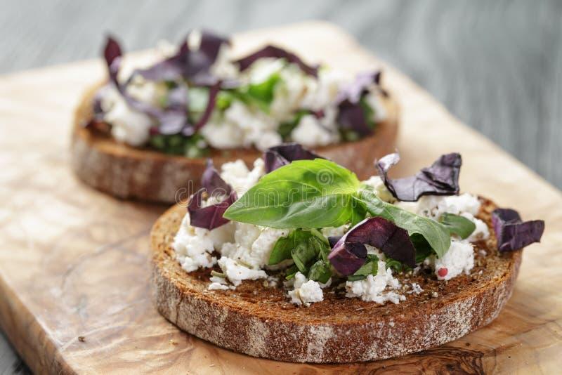 Rågsmörgås eller bruschetta med ricotta, örter och arkivfoto