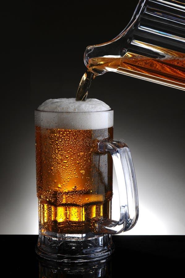 Råna av öl, och kannan häller royaltyfri bild