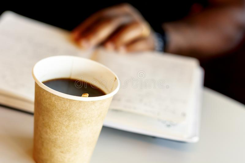 Råna av kaffe med en svart man som läser en bok royaltyfri bild