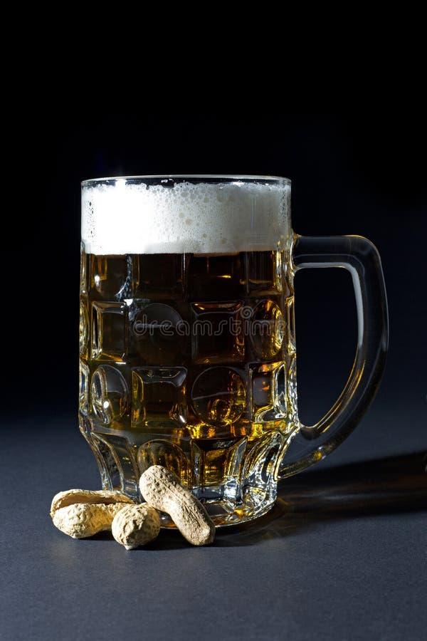 Råna av nytt öl med skum och jordnöten i Shell Isolated på svart royaltyfri fotografi
