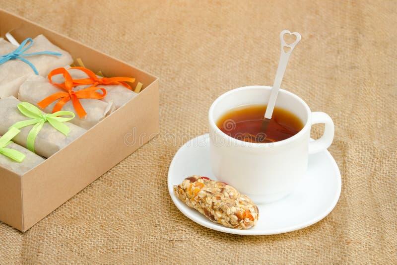 Råna av te, en stång av mysli och askar av stänger sackcloth royaltyfria foton
