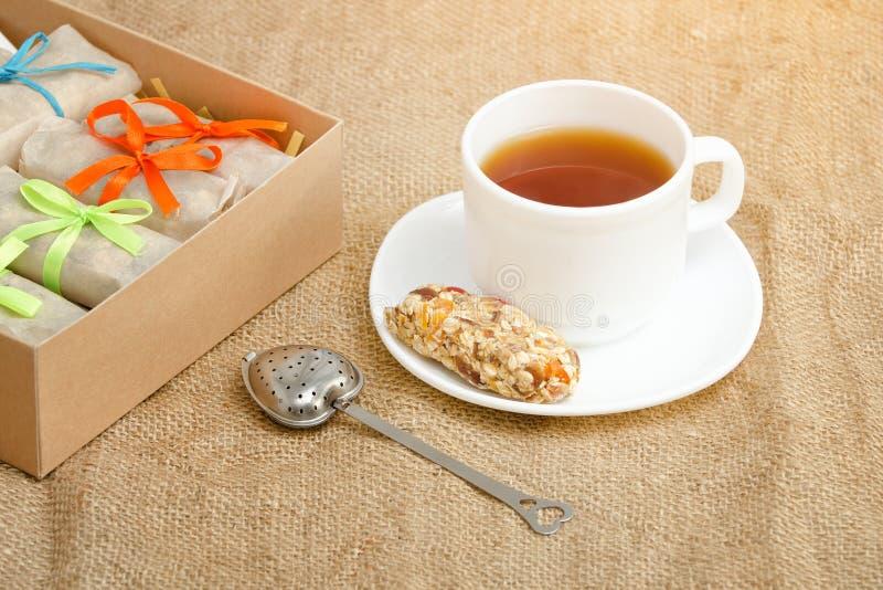 Råna av te, en stång av mysli och askar av stänger sackcloth arkivbild