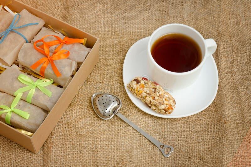 Råna av te, en stång av mysli och askar av stänger sackcloth arkivbilder