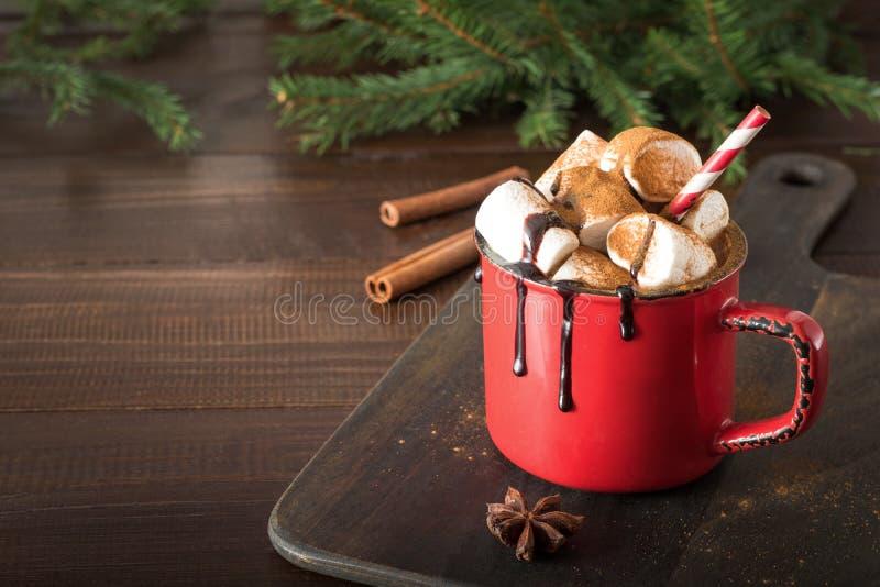 Råna av varm choklad och kakao med marshmallower med julträdfilialer på träbräde Xmas-ferie royaltyfria foton