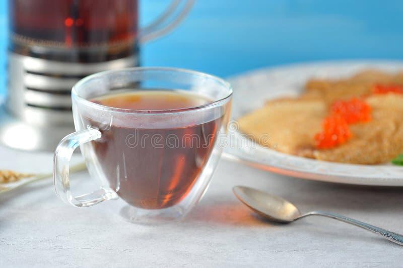 Råna med te och pannkakor i en platta med kaviaren arkivfoto