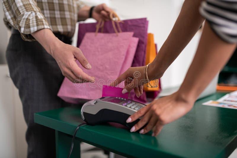 Råna skottet av köparen som gör betalning med en kreditkort arkivbilder