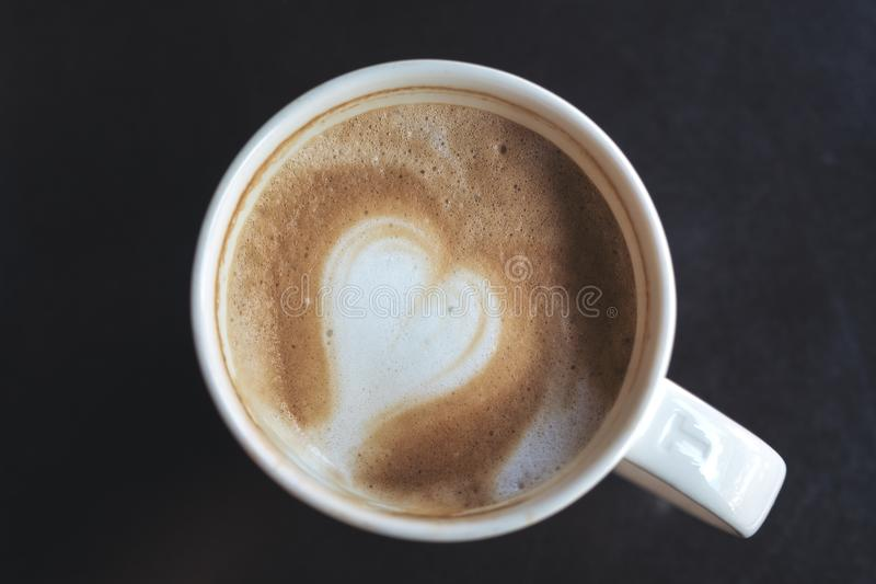 Rånar den övre bilden för slutet av varmt kaffe med hjärtalattekonst i vit arkivbild