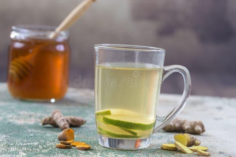 Rånar den stärkande drinken för energi med gurkmeja, ingefäran, citronen och honung i exponeringsglas, trätabellen royaltyfria foton