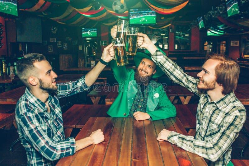 Rånar rymma för tre lyckligt ungt vänner av öl tillsammans ovanför tabellen i bar Folkleende Grabb i mellersta kläderSt Patrcik arkivfoto