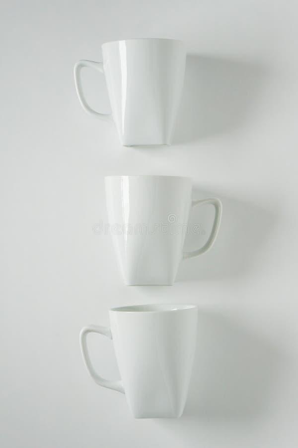 rånar vitt kaffe 3 på vit bakgrund i en vertikal rad, tomt kopieringsutrymme royaltyfri foto