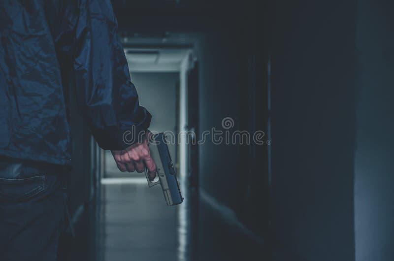 Rånare eller gangster, tjuvinnehavvapen i handsida honom som är klar att skjuta, mord, brott arkivfoto