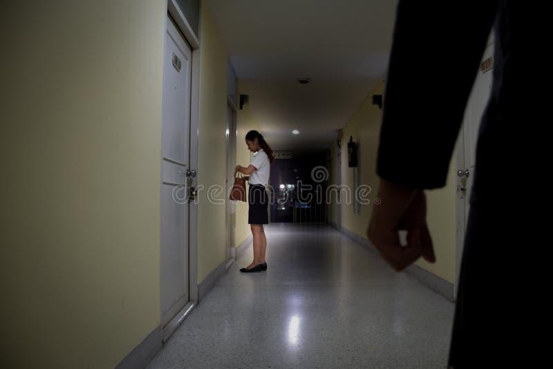 Rånare- eller tjuvhand som ser till affärskvinnan som som ser i påse på dörren på natten, fokus på folk, brottsligt begrepp royaltyfri foto