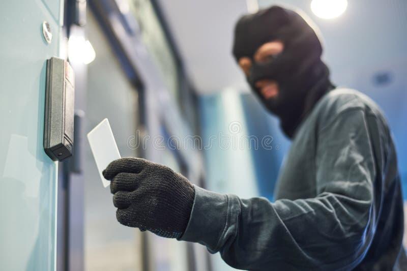 Rånare som använder den elektroniska tangenten för acceess arkivfoto