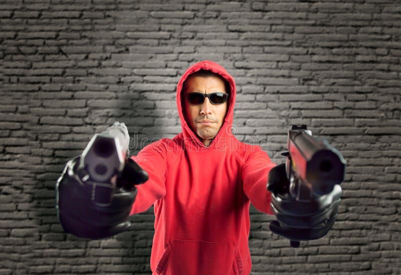 Rånare som pekar två vapen arkivfoton