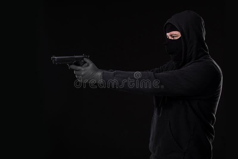 Rånaren i en maskering med ett vapen som pekas till sidan på en svart bakgrund royaltyfri bild
