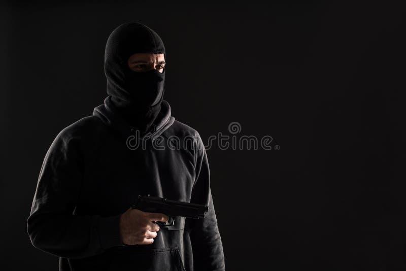 Rånaren i en maskering med ett vapen som pekas till sidan på en svart bakgrund arkivfoton